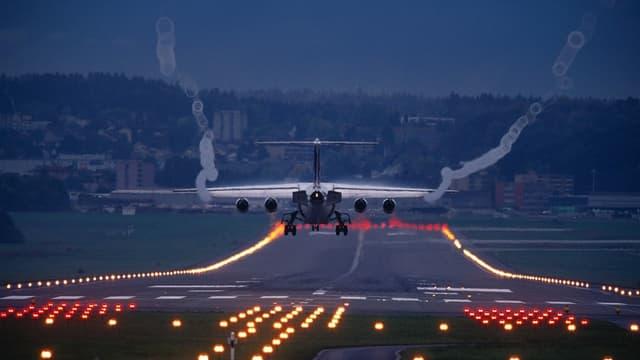Ein Flugzeug landet auf einer beleuchteten Piste auf dem Flughafen Zürich