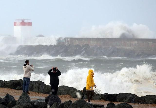 Leute an der Küste betrachten die Wellen.