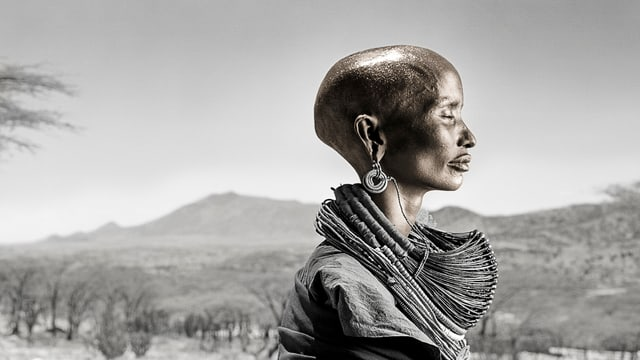 Seitenansicht einer jungen, dunkelhäutigen Frau mit kahlem Kopf.