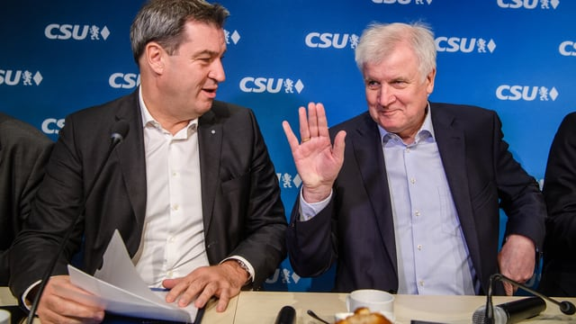 Zwei Männer, der ältere (Seehofer) winkt.