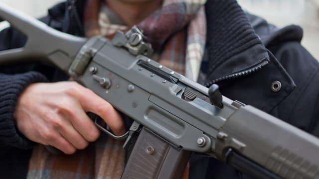 Mann mit Waffe. Sturmgewehr 90. Seriennummer wegbearbeitet.