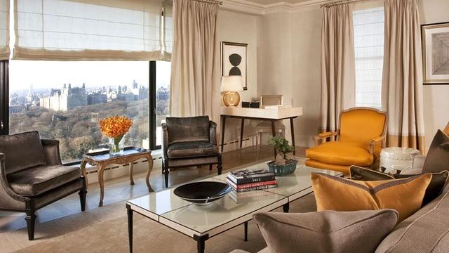 Ein nobles Wohnzimer mit bequemen Sesseln und einem Sofa. Ein grosses Fenster mit Blick auf den Central Park.