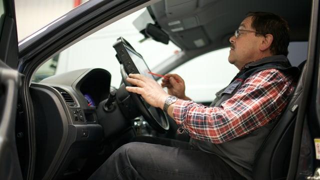Garagist Schär sitzt im Auto und tippt auf ein Tablet-Computer.