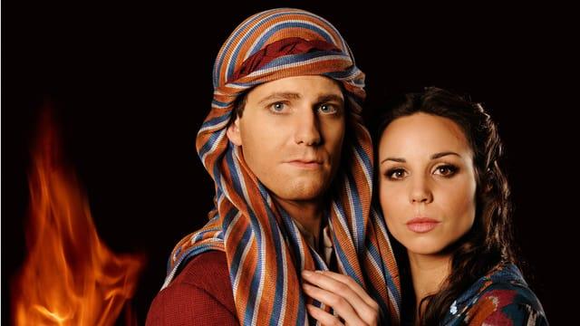 Die Musicaldarsteller der Figuren Moses und Ziphora in Kostümen, im Hintergrund eine Flamme.