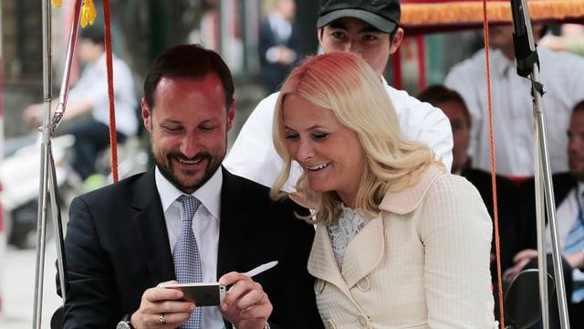 Kronprinz Haakon und Kronprinzessin Mette-Marit betrachten ihr Selfie.