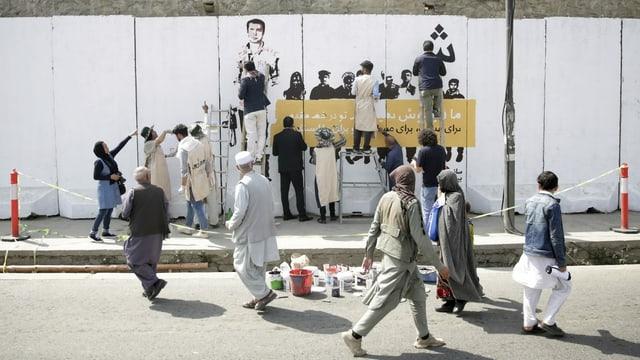 Menschen vor einer Wandmalerei