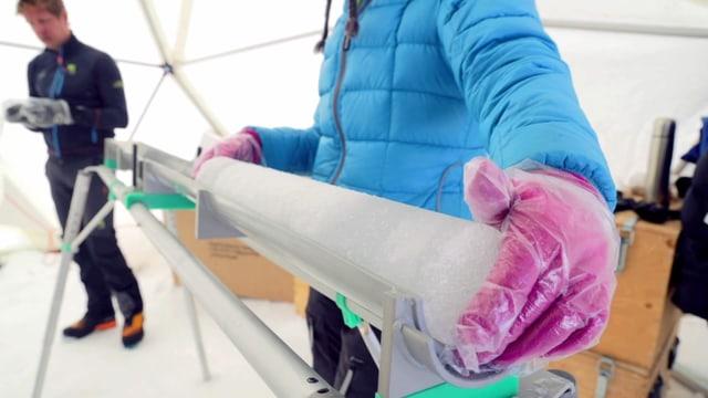 Eine Person nimmt aus einer langen Metallröhre einen länglichen Eiszylinder
