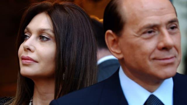Lario, links im Bild, schaut von Berlusconi weg.