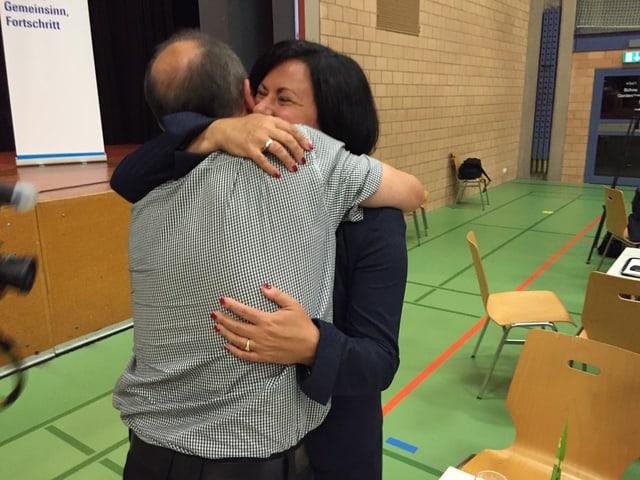 Meister und ihr Mann umarmen sich.