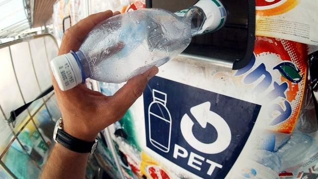 Persuna che bitta ina buttiglia PET en in cecicladi.