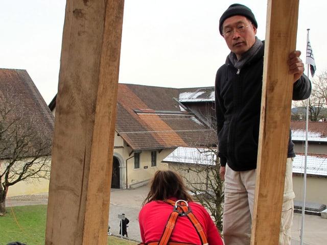 Der japanische Künstler Tadashi Kawamata und zwei Helfer auf dem Holzberg.