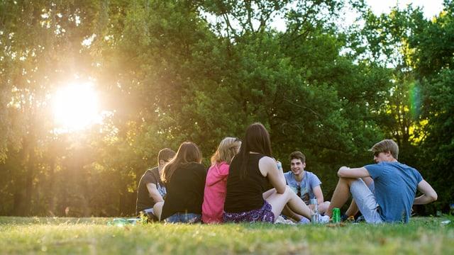 Jugendliche sitzen auf Rasen