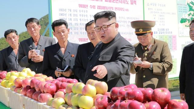 Kim umgeben von mehreren Männern, einige notieren eifrig in kleine Büchlein, sie stehen vor Kisten mit frisch geernteten Äpfeln..