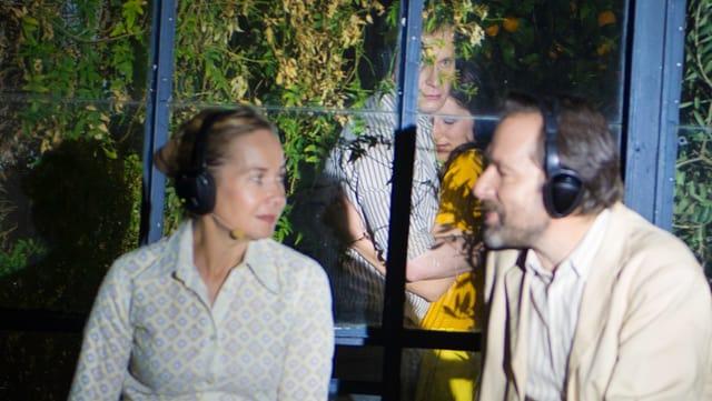 Ein Paar unterhält sich - sie tragen Kopfhörer mit einem angeschlossenen Mikrofon