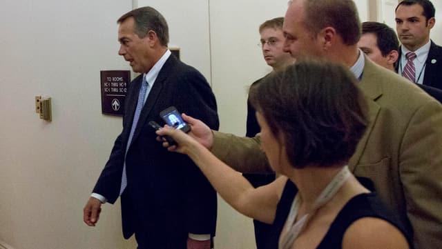 John Boehner von Journalisten begleitet in einem Gang zwischen Büros.