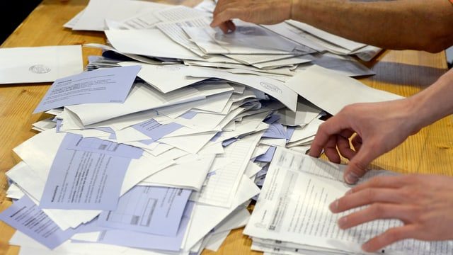 Dus mauns che sorteschan scrits da votaziuns ed elecziuns.