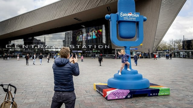 Mann mancht Foto von Kind vor grossem blauen Mikrofpn vor Festhalle.