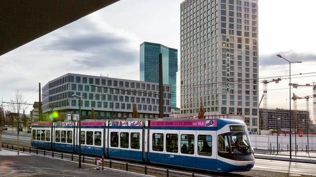Das neue Tram Zürich West auf der Fahrt mit Hochhäusern im Hintergrund.