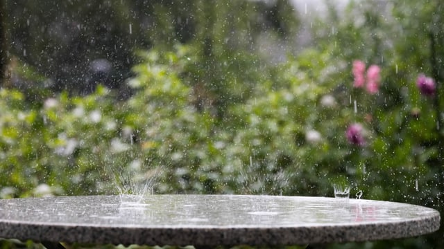 Die Regentropfen zerplatzen auf einem Steintisch in Muttenz.