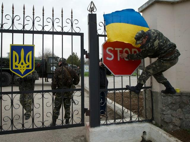 Soldat befestigt ukrainische Flagge an einem Kasernentor.