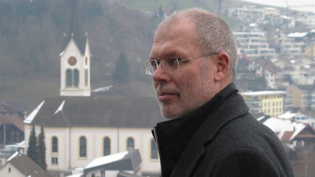 Der Gemeindepräsident von Menznau, Adrian Duss, im Hintergrund die Kirche von Menznau.