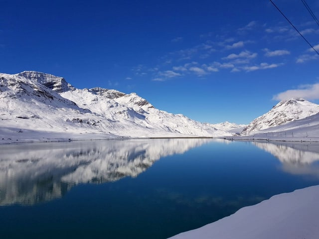 Der Stausee im Berniangebiet ist noch nicht zugefroren, die Berge rund um sind mitNeu schee bedeckt.