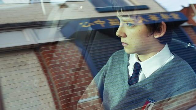 Ein Junge in Schuluniform blickt abbwesend hinter einer Auto-Scheibe geradeaus.