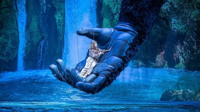 Eine Frau räkelt sich in der riesigen Hand eines Affen.