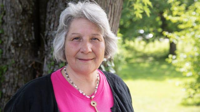 Lilian Senn steht vor einem Baum in einem Park