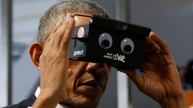 Barack Obama ein Gerät vor den Augen haltend.