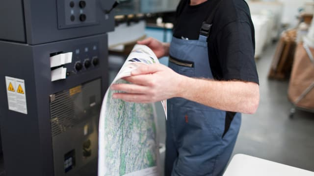 Ein Arbeiter hält einen Druck-Bogen.