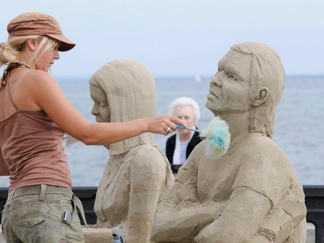 Künstlerin arbeitet an einer Sandfigur.