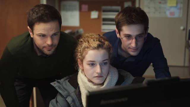 Jane an ihrem Bürotisch mit zwei männlichen Kollegen im Nacken.