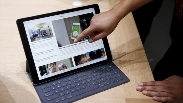 Eine Hand zeigt auf das neue iPad Pro, das in seiner Tastatur-Hülle steckt.