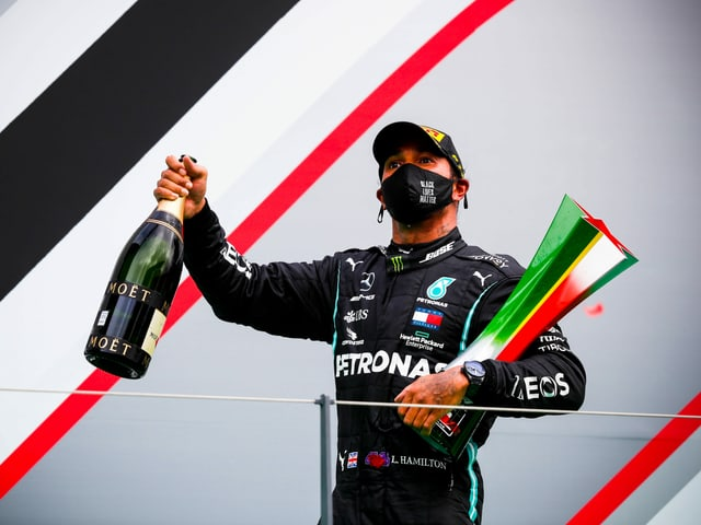 Lewis Hamilton mit Pokal und Schampus.