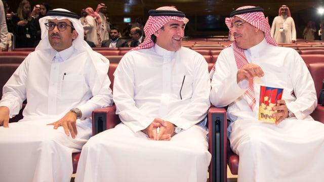 Drei Saudis sitzen mit Popcorn im Kino.