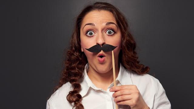 Eine Frau trägt einen falschen Schnurrbart