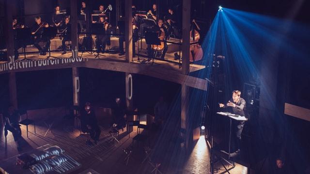 Ein dunkler Bühnenraum. Ein Dirigent dirigiert ein Orchester, das hinter ihm spielt.