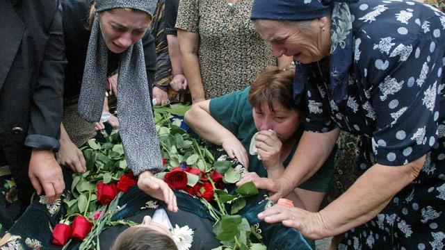 Beslan am 5. September 2004. Angehörige Frauen trauern um das tote Kind, das hier aufgebahrt ist. (reuters)