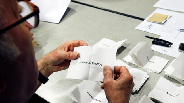 Wahlhelfer zählt Wahlzettel aus.