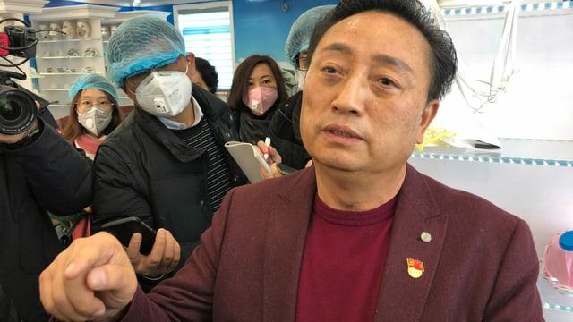 Direktor Wu ohne Gesichtsmaske, dahinter offensichtlich Journalisten, mit Gesichtsmasken.
