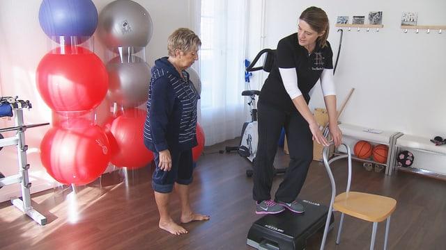 Eine Physiotherapeutin zeigt einer Patientin eine Übung gegen Wadenkrämpfe.