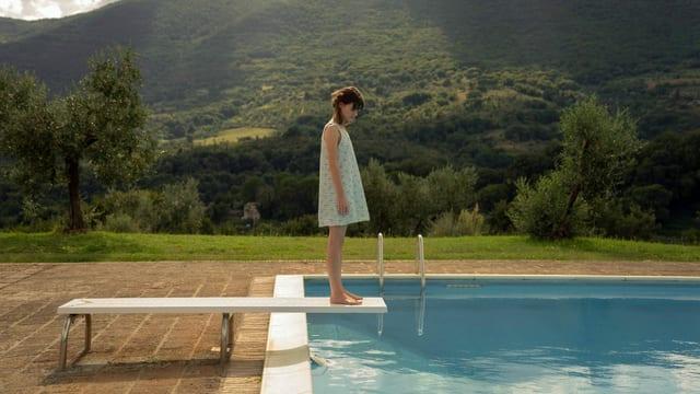 Eine junge Frau steht in einem Sommerkleid auf einem Pool-Sprungbrett vor einer hügelig-ländlichen Kulisse.