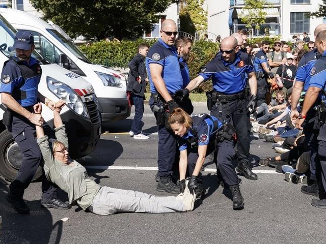 Polizei trägt Frau weg, die an Sitzstreik auf Strasse teilgenommen hatte.