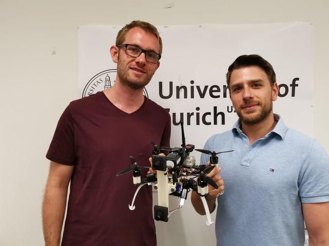 Zwei Männer, die zwischen sich eine Drohne halten.