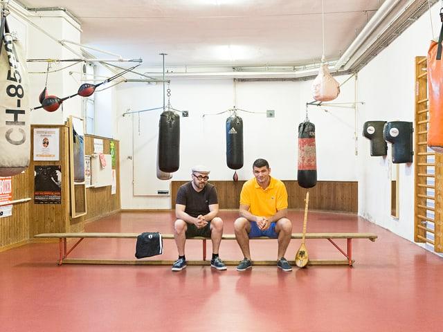 Angelo Gallina und Arnold Gjergjaj sitzen auf einer Bank im Box-Club.
