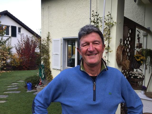 Mann in Pullover steht vor einem Haus, daneben Garten