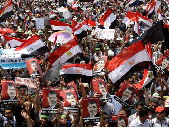 Tausende halten Plakate und Banner in die Höhe