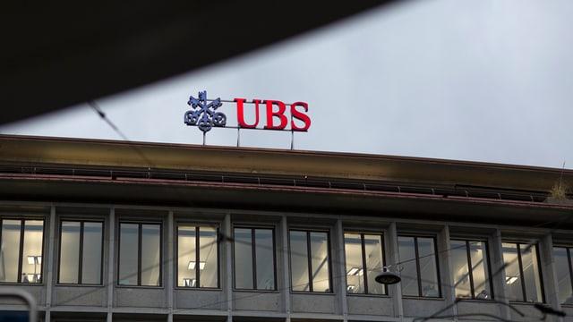 Il logo da la UBS sin il tetg da la sedia centrala da la banca a Turitg. Ins vesa las cazzolas da l'etascha il pli sisum dal bajetg èn illuminadas. Il tschiel è grisch. Il rest dal bajetg na vesan ins betg.