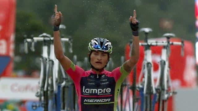 Der kolumbianische Radfahrer Winner Anacona streckt bei dem Überqueren der Ziellinie beide Hände in die Luft.